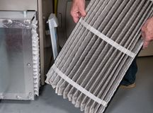 Senior man changing a dirty air filter in a HVAC Furnace. Senior caucasian man examining a folded dirty air filter in the HVAC furnace system in basement of home stock photography