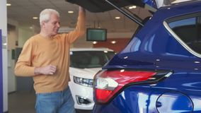 Senior man opens car trunk at the dealership. Senior caucasian man opening car trunk at the dealership. Gray male customer raising the tailgate of purple Royalty Free Stock Photos