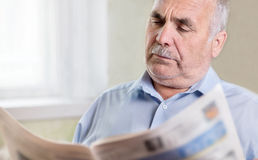 Senior Caucasian Man Reading A Newspaper At Home Royalty Free Stock Photo