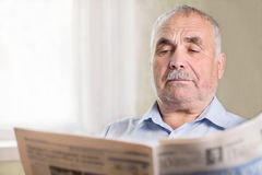 Senior Caucasian man reading a newspaper at home Stock Photo