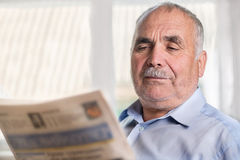 Senior Caucasian man reading a newspaper at home Stock Photography