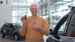 Senior man shows thumb up at the dealership. Senior caucasian man showing his thumb up at the dealership. Aged male customer standing near the new purple Royalty Free Stock Image