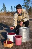 Senior Caucasian man showing red bilberry in hand. Full buckets and basket Royalty Free Stock Image