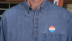 Senior caucasian man in working clothing with Voted sticker royalty free stock image