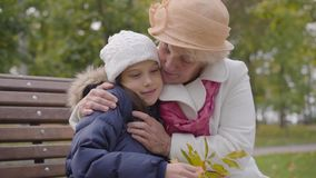 Senior Caucasian woman in beige cloche hat and white coat fixing the white hat of her granddaughter. Happy grandmother. Sitting with young pretty girl on the stock footage