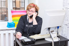 Senior Caucasian woman calling on telephone in office room Stock Photos