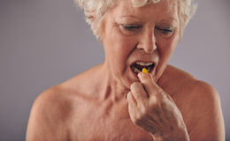 Senior caucasian woman having a pill Stock Images