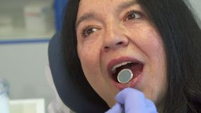 Woman opens her mouth for dental check up stock images