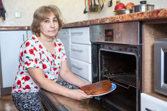 Senior Caucasian woman with a pie in hands sitting beside the built-in oven in the kitchen Stock Photos