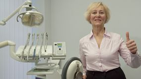 Senior woman shows her thumb up at the dentist office. Senior caucasian woman showing her thumb up at the dentist office. Blond female patient standing near Royalty Free Stock Images