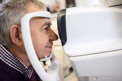 Senior check his sight using apparatus Royalty Free Stock Photography
