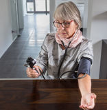 Senior checks blood pressure with measuring instrument on table Stock Photography
