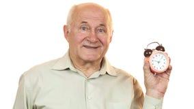 Old man looking at an alarm clock smiling to the camera. Senior cheerful man looking at the alarm clock checking time smiling isolated time management hurry stock image