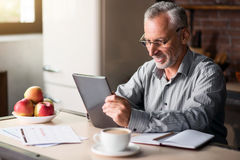 Senior cheerful man using tablet in the kitchen Royalty Free Stock Photos