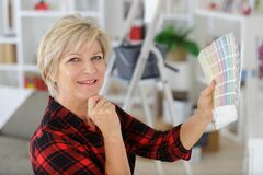 Senior cheerful woman renovate room in new house