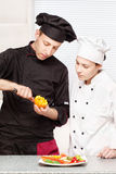 Senior chef teaches young chef to decorate fruit Stock Photo