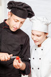 Senior chef teaches young chef to decorate fruit Royalty Free Stock Images