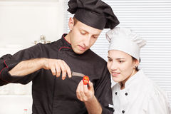 Senior chef teaches young chef to decorate fruit Royalty Free Stock Photography