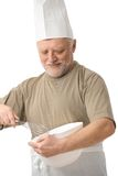 Senior chef whisking egg in kitchen Stock Photos