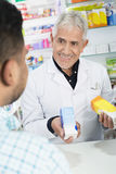 Senior Chemist Holding Products While Looking At Customer Stock Photo