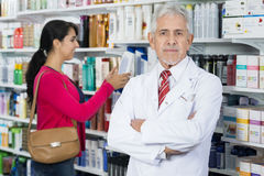 Senior Chemist Standing Arms Crossed While Customer Choosing Pro. Portrait of confident senior chemist standing arms crossed while customer choosing products in Royalty Free Stock Images
