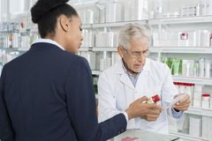 Chemist And Businesswoman With Medicine And Prescription Paper. Senior chemist and young businesswoman with medicine and prescription paper in pharmacy Royalty Free Stock Image