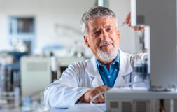 Senior chemistry professor/doctor carrying out research experiments. In an analytical chemistry lab color toned image Royalty Free Stock Images