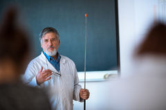 Senior chemistry professor giving a lecture. In front of classroom full of students (shallow DOF; color toned image Royalty Free Stock Image