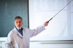 Senior chemistry professor giving a lecture. In front of classroom full of students (shallow DOF; color toned image Stock Photo