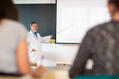 Senior chemistry professor giving a lecture. In front of classroom full of students (shallow DOF; color toned image Royalty Free Stock Photo