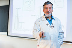 Senior chemistry professor giving a lecture. In front of classroom full of students (shallow DOF; color toned image Royalty Free Stock Photography