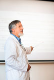 Senior chemistry professor giving a lecture. In front of classroom full of students (shallow DOF; color toned image Royalty Free Stock Images