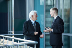 Senior chief and his employee. Talking out of business building stock image
