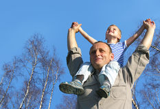 Senior with child on shoulders in front of birch Stock Photo