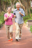 Senior Chinese Couple Jogging In Park Stock Photo