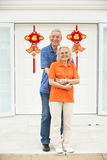 Senior Chinese Couple Outside Home With Feng Shui. Senior Chinese Couple Outside Home Decorated With Welcoming Feng Shui Banners Royalty Free Stock Images