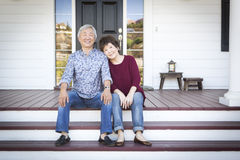 Senior Chinese Couple Sitting on Front Steps of Their House Royalty Free Stock Photography