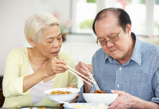 Senior Chinese Couple Sitting At Home Eating Meal Royalty Free Stock Photo