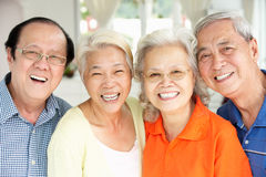 Senior Chinese Friends Relaxing On Sofa At Home Royalty Free Stock Photography