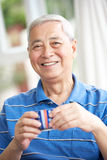 Senior Chinese Man Drinking Tea On Sofa At Home Stock Image