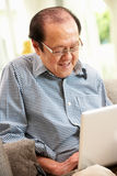 Senior Chinese Man Using Laptop Whilst Relaxing Stock Photo