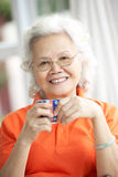 Senior Chinese Woman Drinking Tea On Sofa At Home Stock Photography