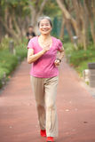 Senior Chinese Woman Jogging In Park Stock Photos