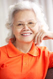 Senior Chinese Woman Relaxing On Sofa At Home Royalty Free Stock Photo
