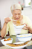 Senior Chinese Woman Sitting At Home Eating Meal Royalty Free Stock Photography