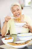 Senior Chinese Woman Sitting At Home Eating Meal Stock Photography