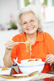 Senior Chinese Woman Sitting At Home Eating Meal Royalty Free Stock Photo