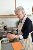 Senior citizen. A senior citizen with the dishes of their dishes stock photo