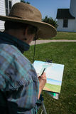 Senior Citizen Artist. A senior who loves watercolor working on her passion at the Tibbetts Point Lighthouse, Cape Vincent, New York stock images