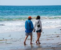 Senior citizen baby boomer male and female caucasian couple walking on the beach towards the ocean holding hands. royalty free stock image